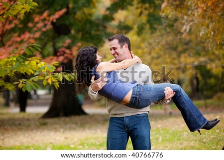 Man holding woman in a park - stock photo