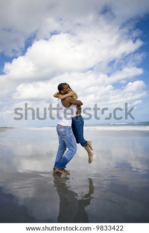 Man holding woman on a beach - stock photo