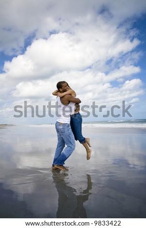 Man holding woman on a beach - stock photo