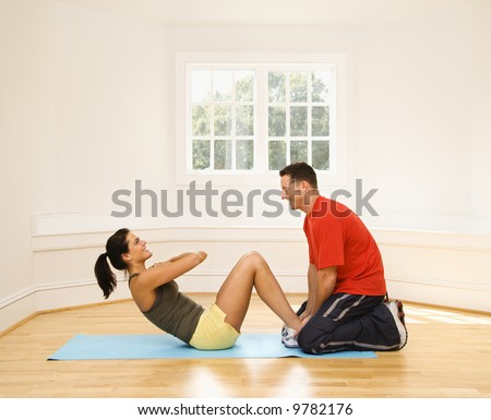 Man holding woman's feet down as she does sit up exercises. - stock photo