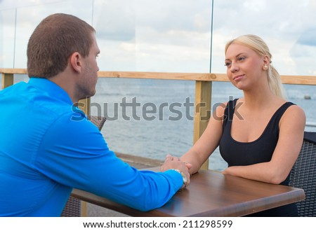 Man holding woman's hand in outdoor cafe. - stock photo