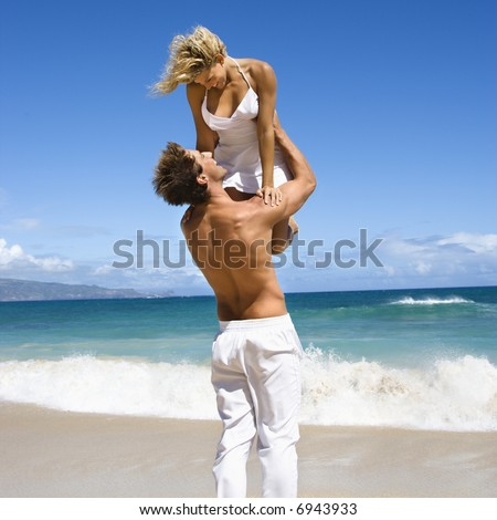 Man holding woman up in air as they look into eachother's eyes on Maui, Hawaii beach.