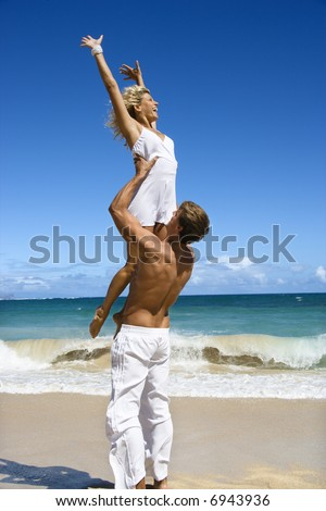 Man holding woman up in air on Maui, Hawaii beach.