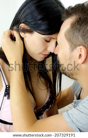 Man holding woman with closed eyes feeling love - stock photo