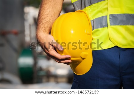 Man holding yellow helmet close up - stock photo