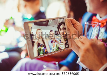 Man holds a champagne flute in one hand and iPad in another