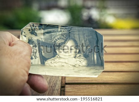 Man holds a  childhood picture of the sixties in his hand. - stock photo