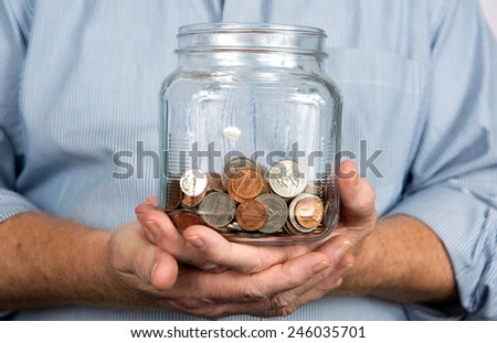 Man holds a glass jar containing United States coins and money. - stock photo
