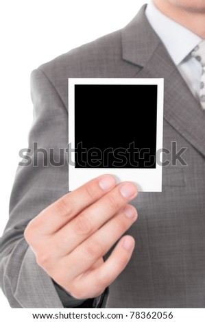 Man holds a instant photo. Focus on instant photo. - stock photo