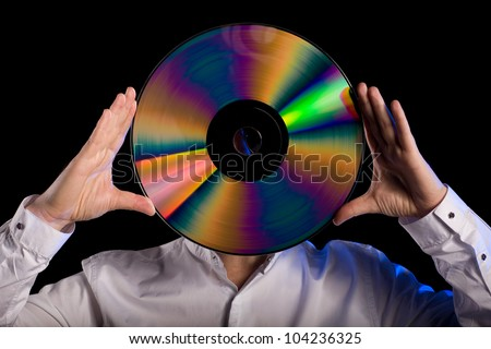 Man holds a retro laser disc instead of the head. - stock photo