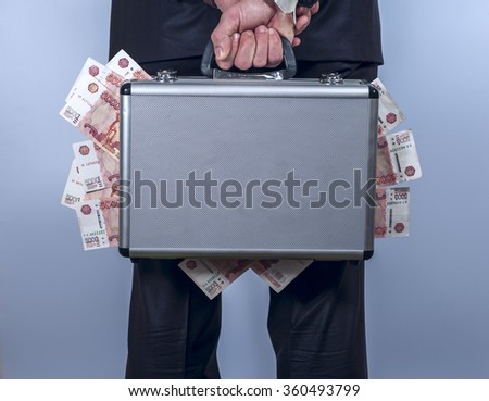 Man holds a suitcase full of money behind the back - stock photo