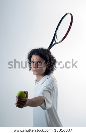 Man holds a tennis ball in one hand and a tennis racket in the other. He has a serious look on his face. Vertically framed photograph - stock photo