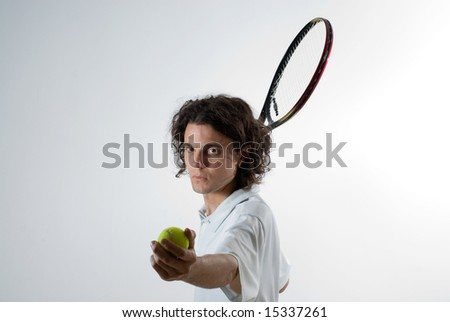 Man holds a tennis racket and ball and is ready to swing. He has an angry expression on his face. Horizontally framed photograph - stock photo