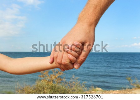 Man holds hand of child on background of sea and sky Concept of love, care, friendship, trust in family. - stock photo