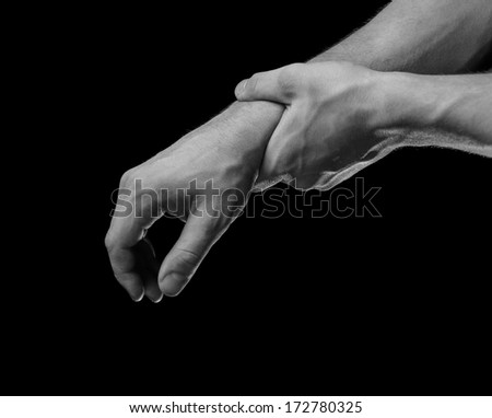 Man holds his hand, acute pain in a wrist, black and white image - stock photo