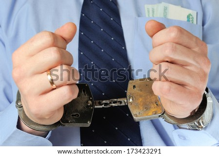 Man holds his hands in handcuffs before itself with money in the pocket - stock photo