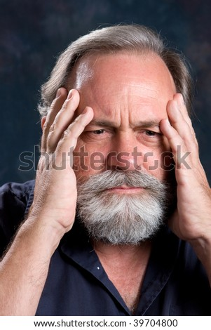 Man holds his head in a state of worry. - stock photo