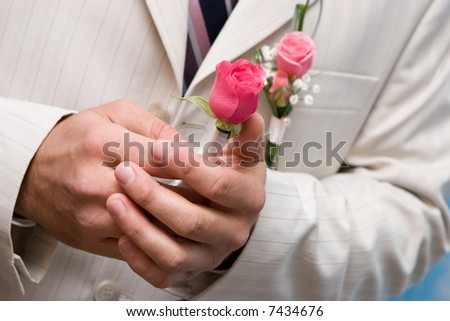 Man holds in hands a small bouquet from red roses