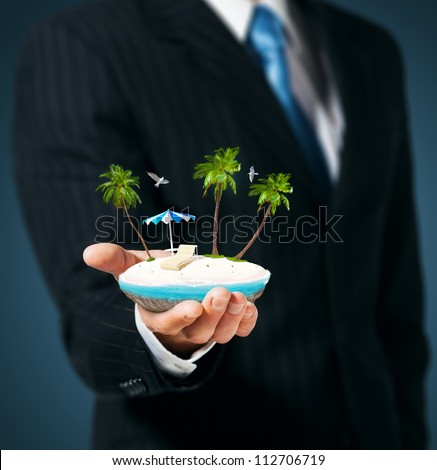 Man holds in his hand a tropical island - stock photo