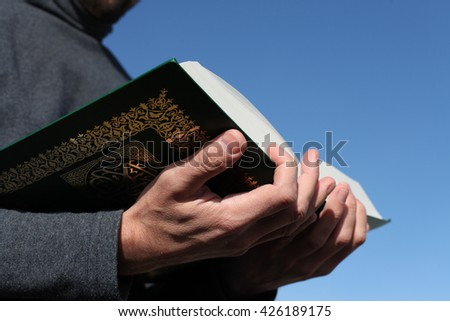 Man holds Koran - holy book of muslims, on blue sky with clouds - stock photo