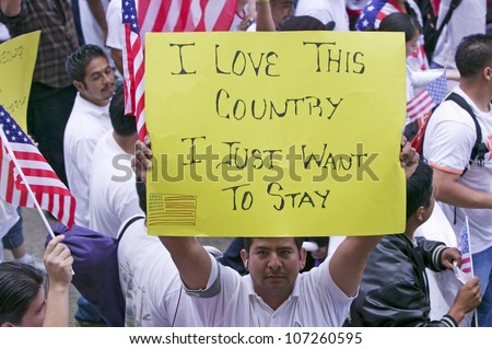 "Man holds sign saying ""I love this country"" in march for Immigrants and Mexicans protesting against Illegal Immigration reform by U.S. Congress, Los Angeles, CA, May 1, 2006 - stock photo"