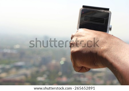 Man holds small extreme digital camera in hand, shooting city in blurry background - stock photo