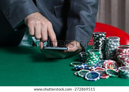 Man holds smartphone, do bet at online casino  - stock photo