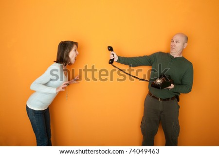 Man holds telephone while woman yells at it