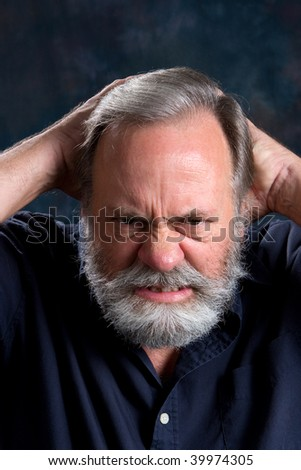 Man holds the back of his head in frustration. - stock photo