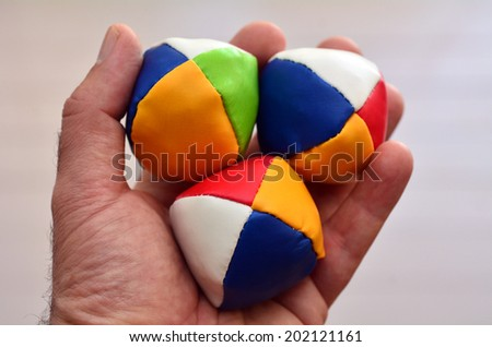 Man holds three (3) Juggling balls on one hand (left) against light background. concept photo, copy space