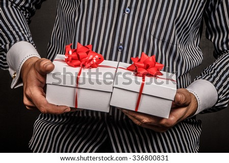 Man holds two gift boxes wit red bows. - stock photo