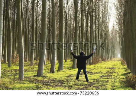 Man holing saws, reading to cut trees; concepts:  environment damages - stock photo