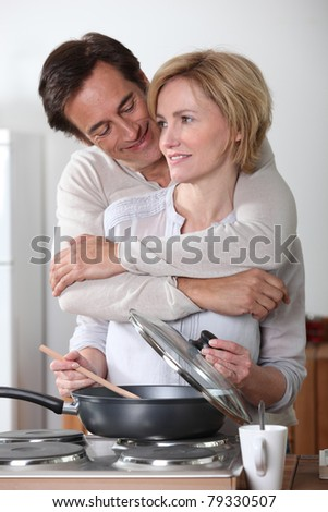 Man hugging a woman cooking at an electric stove