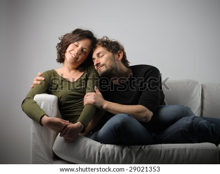 man hugging his girlfriend on a sofa - stock photo