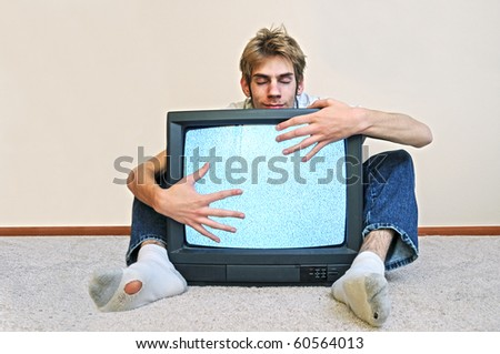 Man hugging his old CRT TV plugged into the wall with static on the screen - stock photo
