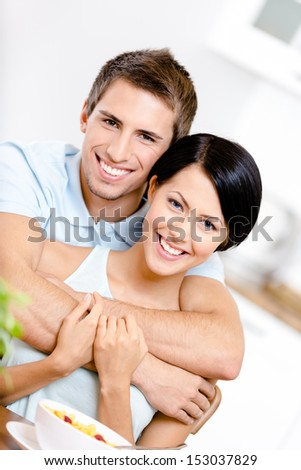 Man hugs his smiley girlfriend in the kitchen - stock photo