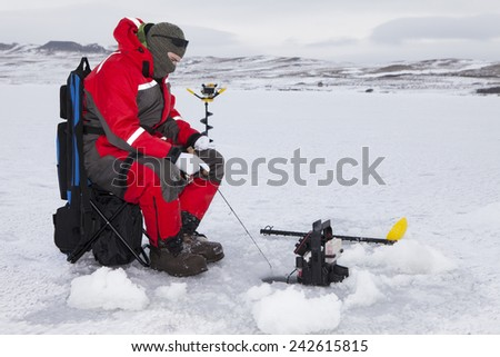 Man ice fishing on a cold winter day. - stock photo