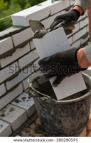 man imposes cement on a brick - stock photo