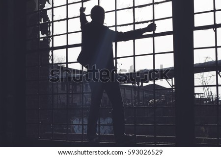 Man imprisoned behind bars looking