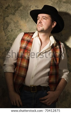 Man in a black hat on a sharpened wall background - stock photo