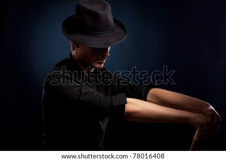 man in a black hat on black background - stock photo