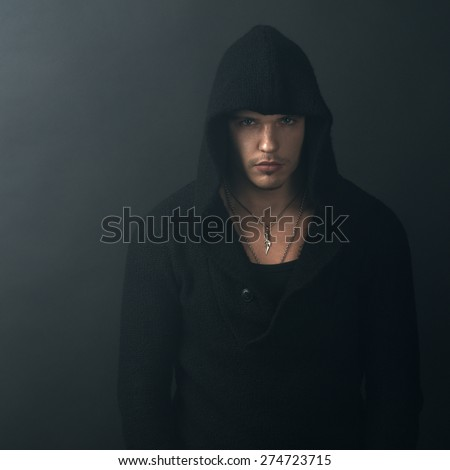 man in a black hoodie looking confidently - stock photo