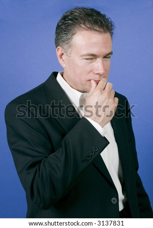 Man in a black suit with an expression on his face as if he is dealing with a tricky question - stock photo