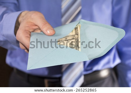 Man in a blue shirt, giving bribe in a blue envelope - stock photo