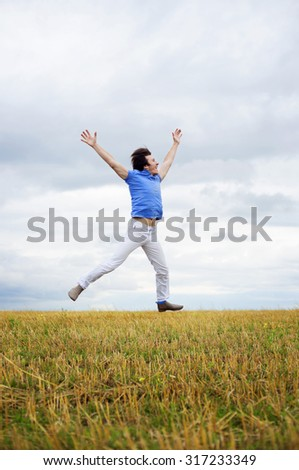 Man in a blue shirt jumping against cloudy sky  - stock photo