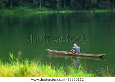 man in a boat floating on the river - stock photo