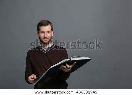 Man in a brown sweater casual business enthusiastically reading a great book, a teacher, scientist