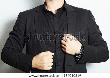 man in a business suit and black shirt.watch.fashion.hands.without face.stylish businessman.man in the suit on white - stock photo