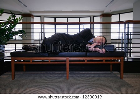 Man in a business suit asleep on a couch in an office hallway - stock photo