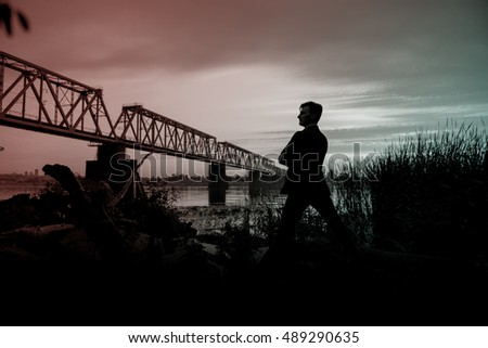 man in a business suit near the river, city bridge background.